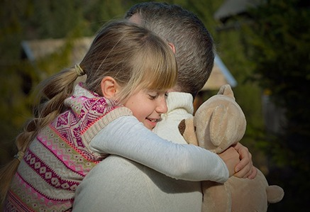 father holding daughter with teddy bear