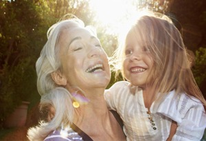 grandmother and granddaughter smiling in the sun
